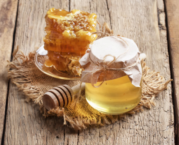 Honey jar and honeycomb, vintage wooden kitchen table background, copy space, selective focus